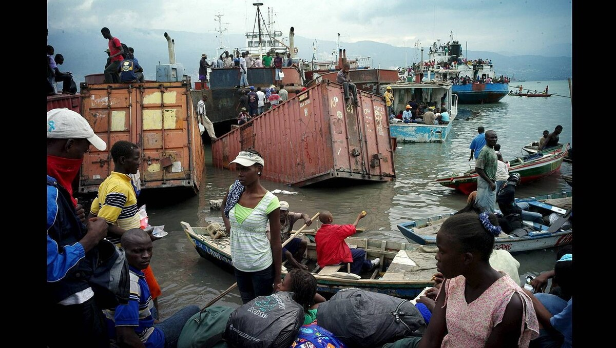 A Haitian family, trying to leave the city, prepares to board a boat Jan. 19, 2010 in the harbor of Port-au-Prince. Thousands of residents fled the city after the quake.