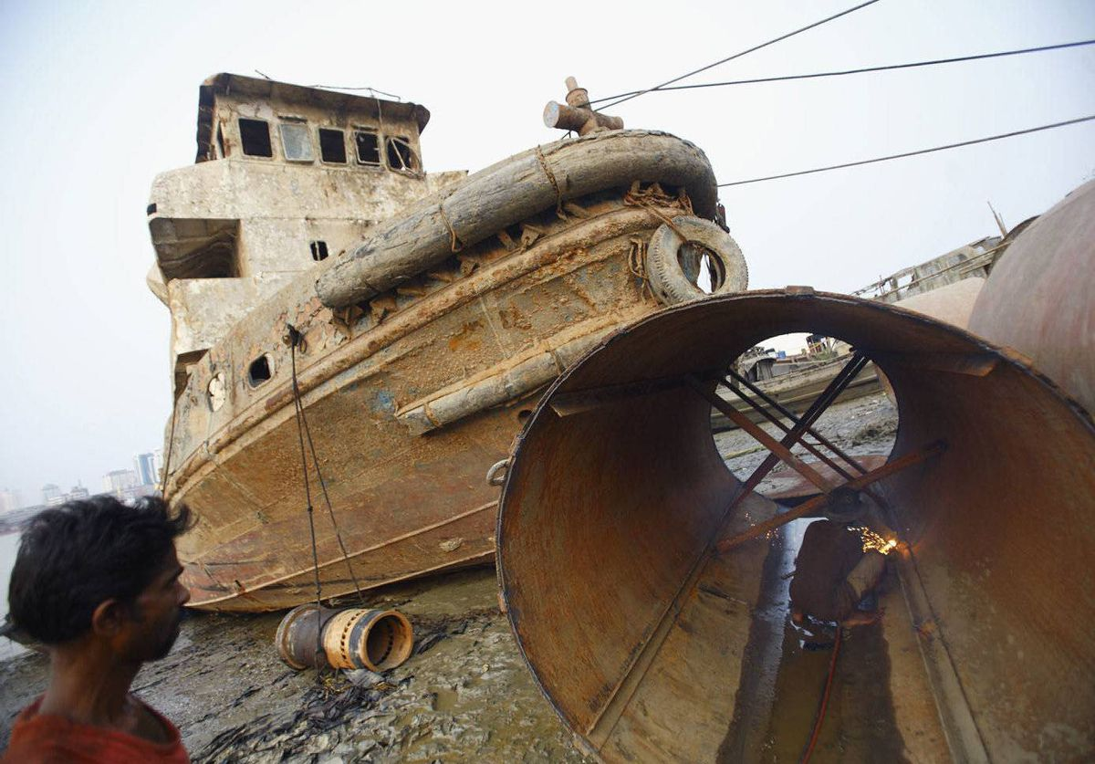 Workers work on an old ship on the banks of the Yangon River in Yangon, Myanmar.