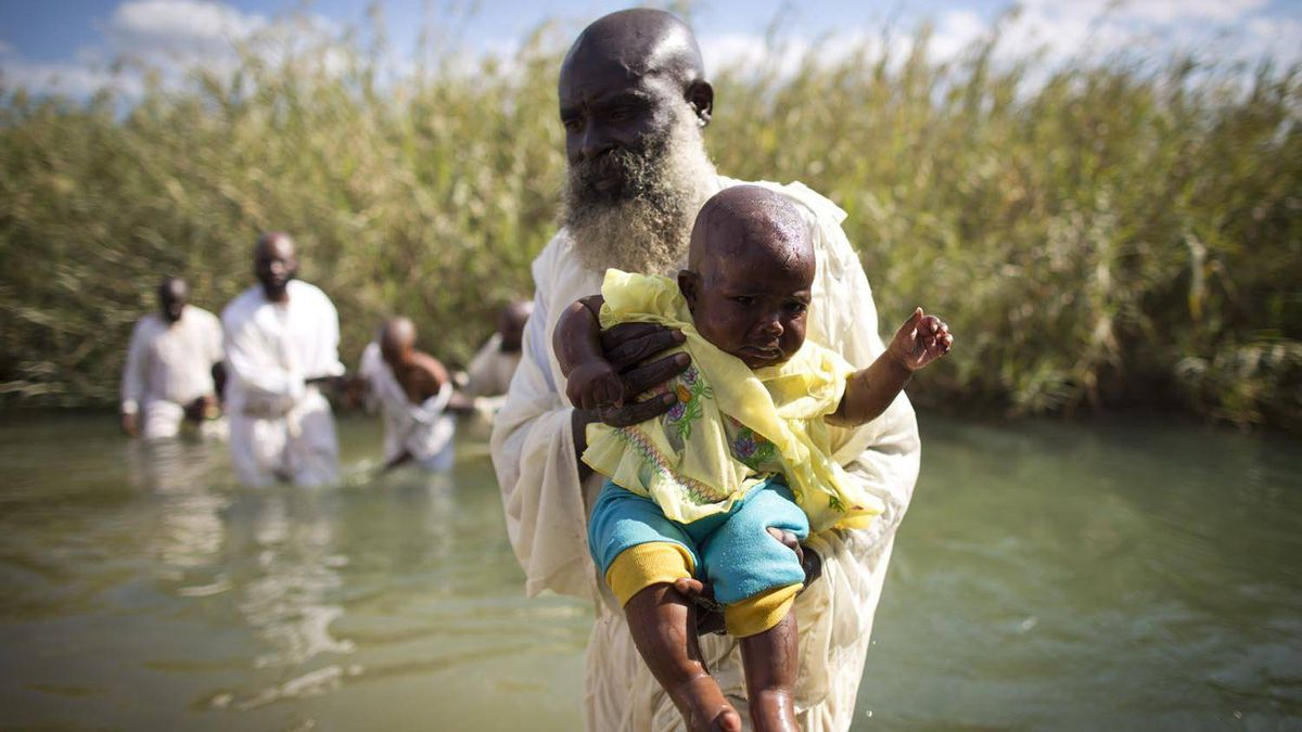 A priest baptizes a child in a river outside Lubumbashi, in the Democratic Republic of the Congo. Many Christian sects in the Congo refuse blood transfusions, creating problems for malaria treatment.