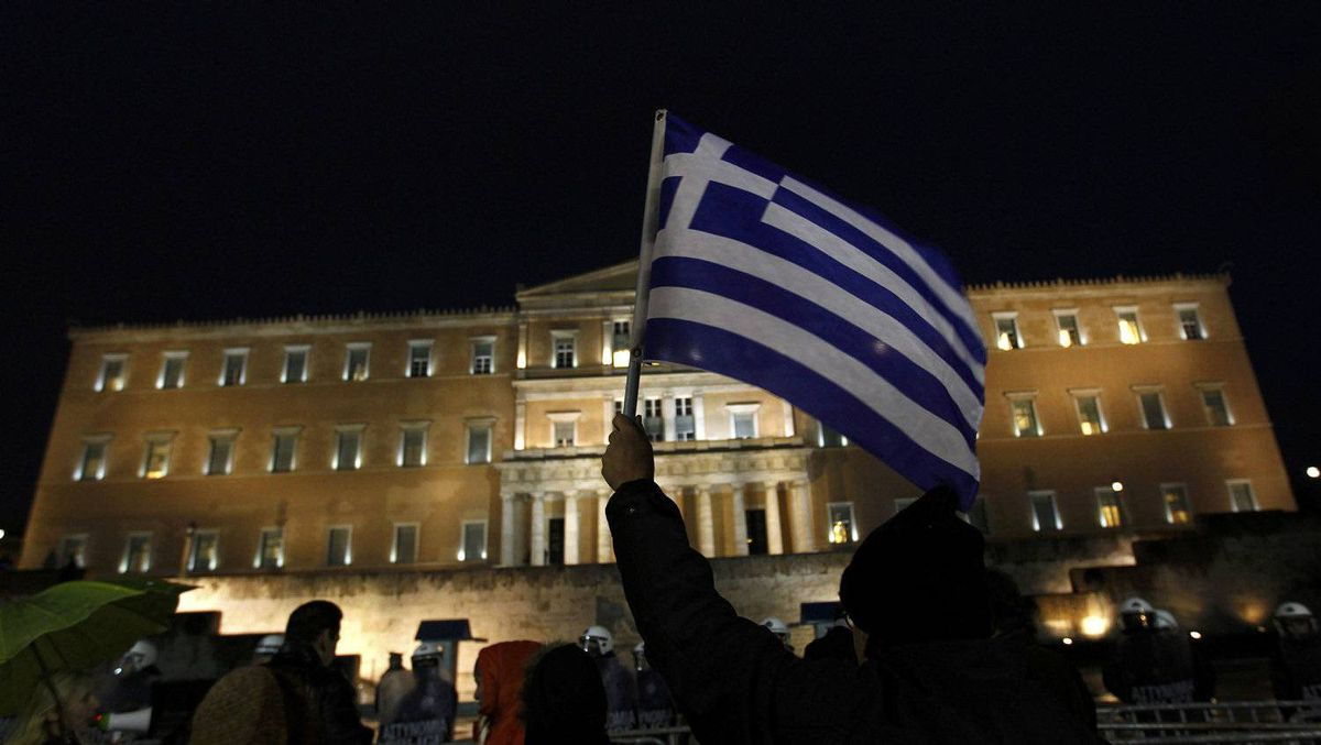 A protester holds up a Greek flag during an anti-austerity demonstration in front of the parliament in Athens Feb. 22, 2012.