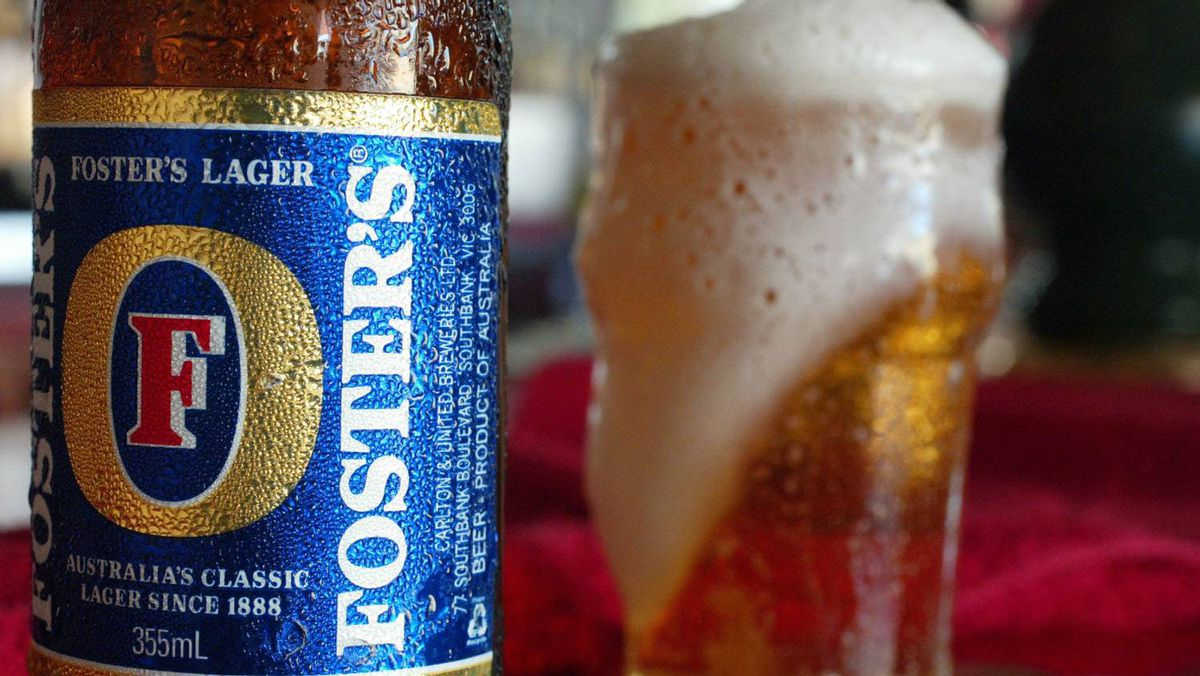 A bottle of Foster's beer stands near a freshly poured glass of beer at a hotel bar in Sydney.