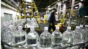 Plastic bottles filled with soda prior to be labelled are carried on conveyor belt at the soft drink maker Cott's bottling plant.