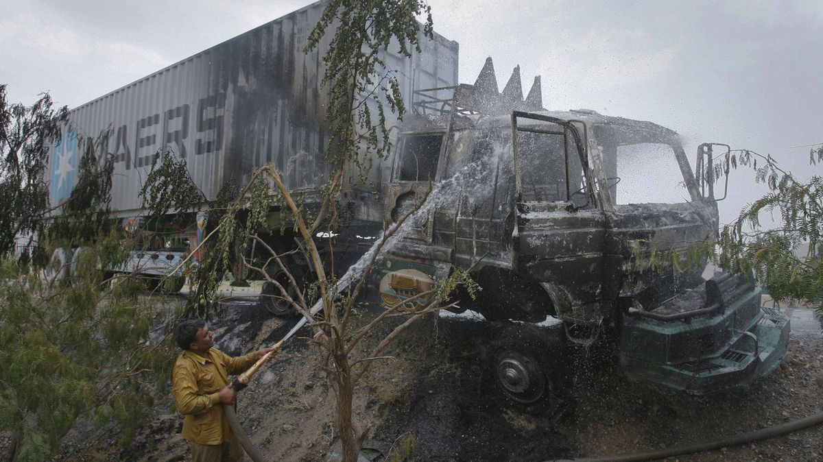 A firefighter sprays water on a truck which was set ablaze by gunmen in Quetta July 11, 2011. Six men on three motorbikes fired on a NATO truck carrying supplies for foreign troops in Afghanistan.
