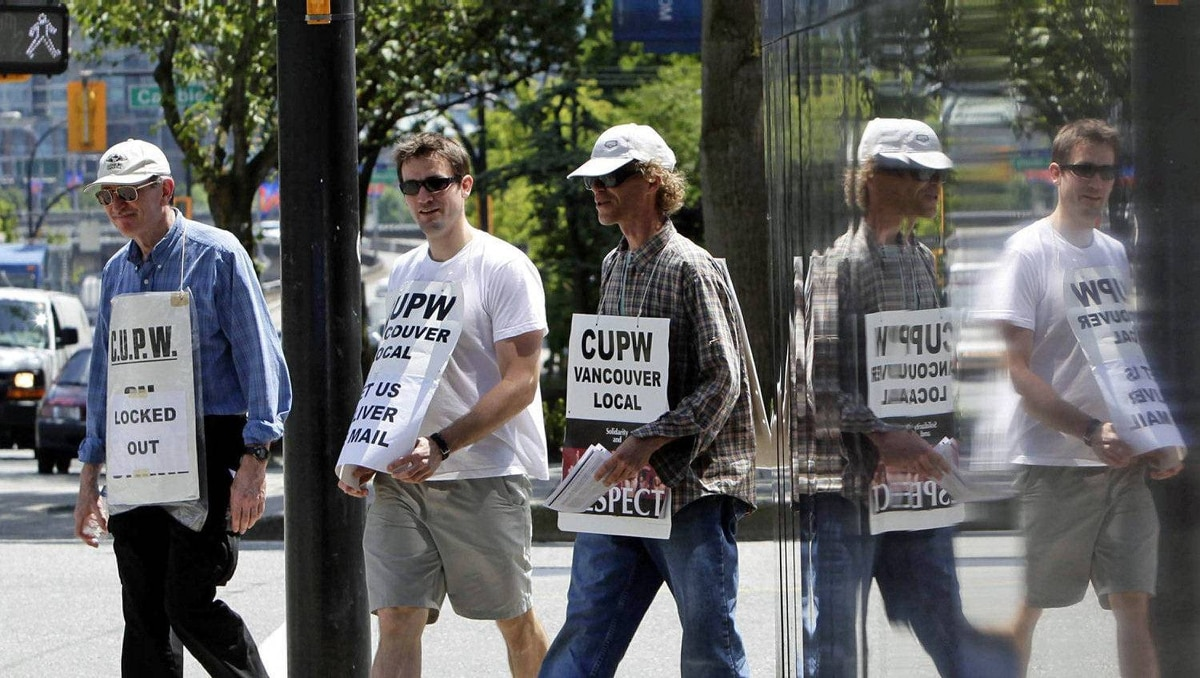 Locked out Canada Post workers picket outside Vancouver main post office on June 21, 2011.