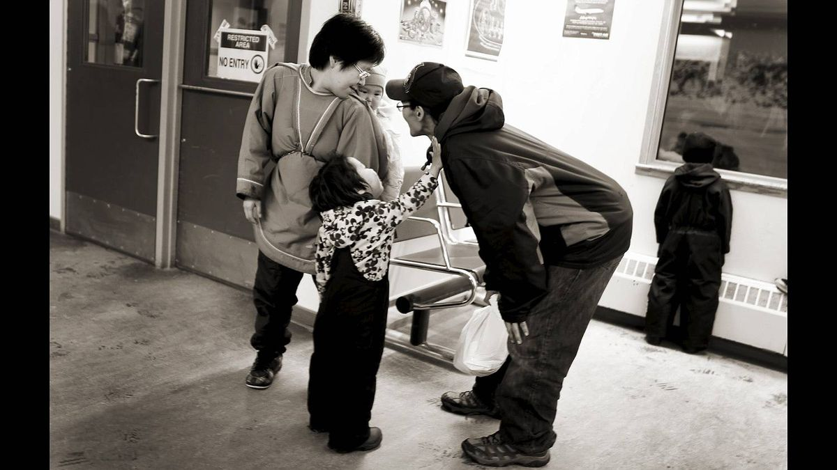 A man who had just stepped of a flight from Iqaluit greets his family inside the small airport in Cape Dorset, Nunavut on November 11, 2010.