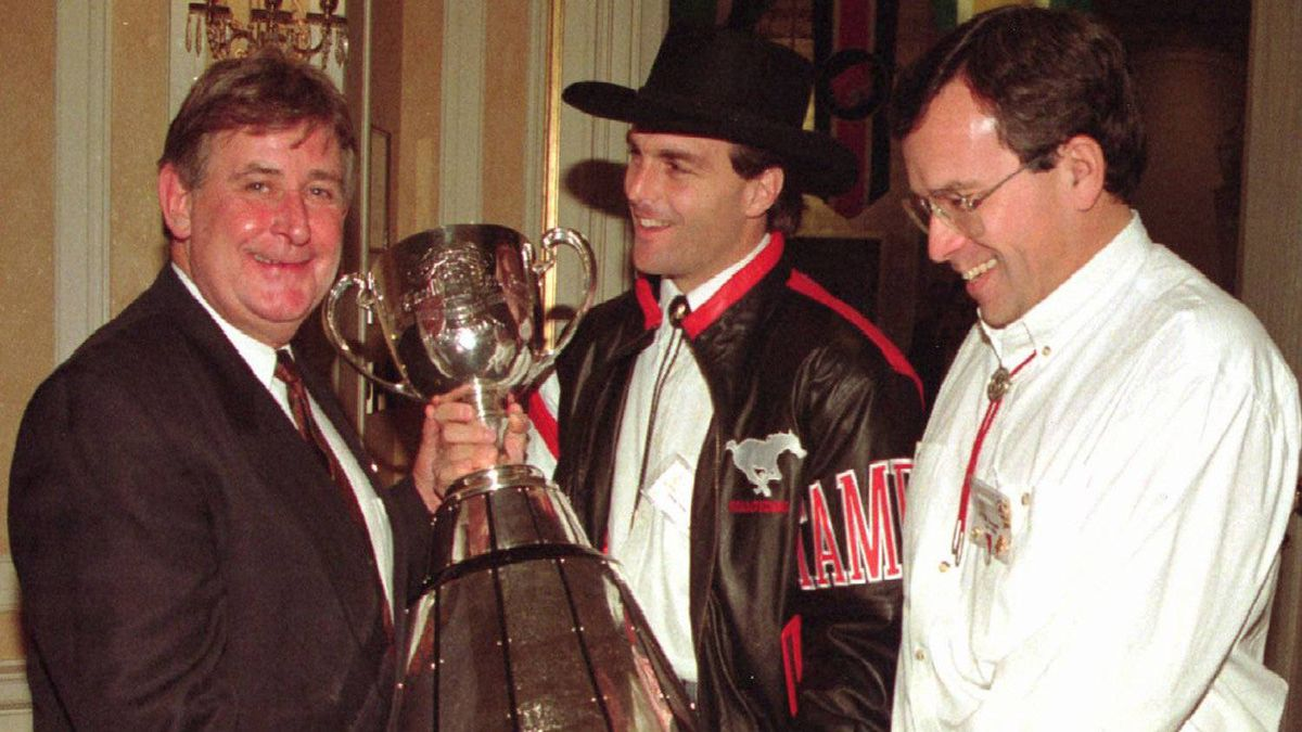 Mr. Klein joins Calgary Stampeders quarterback Doug Flutie and Manitoba Premier Gary Filmon to pose for photographers with the Grey Cup prior to the Premiers Grey Cup luncheon in 1993.