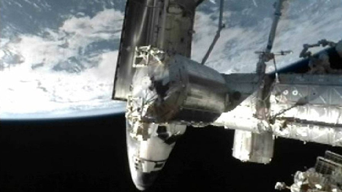 The space shuttle Atlantis is seen docked to the International Space Station with the earth in the background in this image from NASA TV July 10, 2011.
