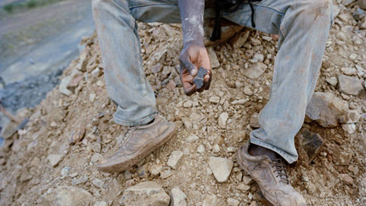 A mine intruder sits on waste rock searching for rocks containing gold deposits at the North Mara Mine in Tanzania.