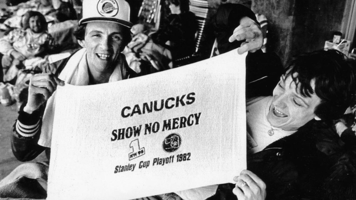 A couple of Vancouver Canuck fans proudly display one of the towels that they and thousands of others will use to cheer on the Canucks in their first home game of the Stanley Cup playoffs here 5/13. These fans have been in the line-up for tickets to that game since 5/10. Credit: Nick Didlick / UPC