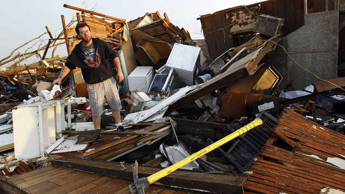 Mark Langford sorts through the debris looking for personal belongings after his home was destroyed when a tornado hit Joplin, Missouri May 23, 2011.