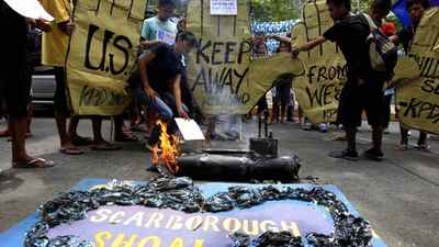 Protesters display placards and a replica of the disputed Scarborough Shoal in the South China Sea as they burn an effigy of a U.S. submarine USS North Carolina, currently on a port call in the country, during a rally at the U.S. embassy in Manila, on May 17.