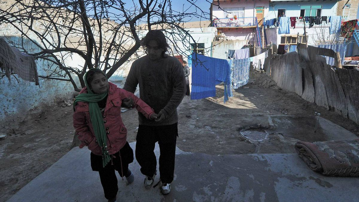 Twelve-year-old Tarana Akbari (L) walks in the yard with the help of her uncle outside her home in Kabul on December 10, 2011.