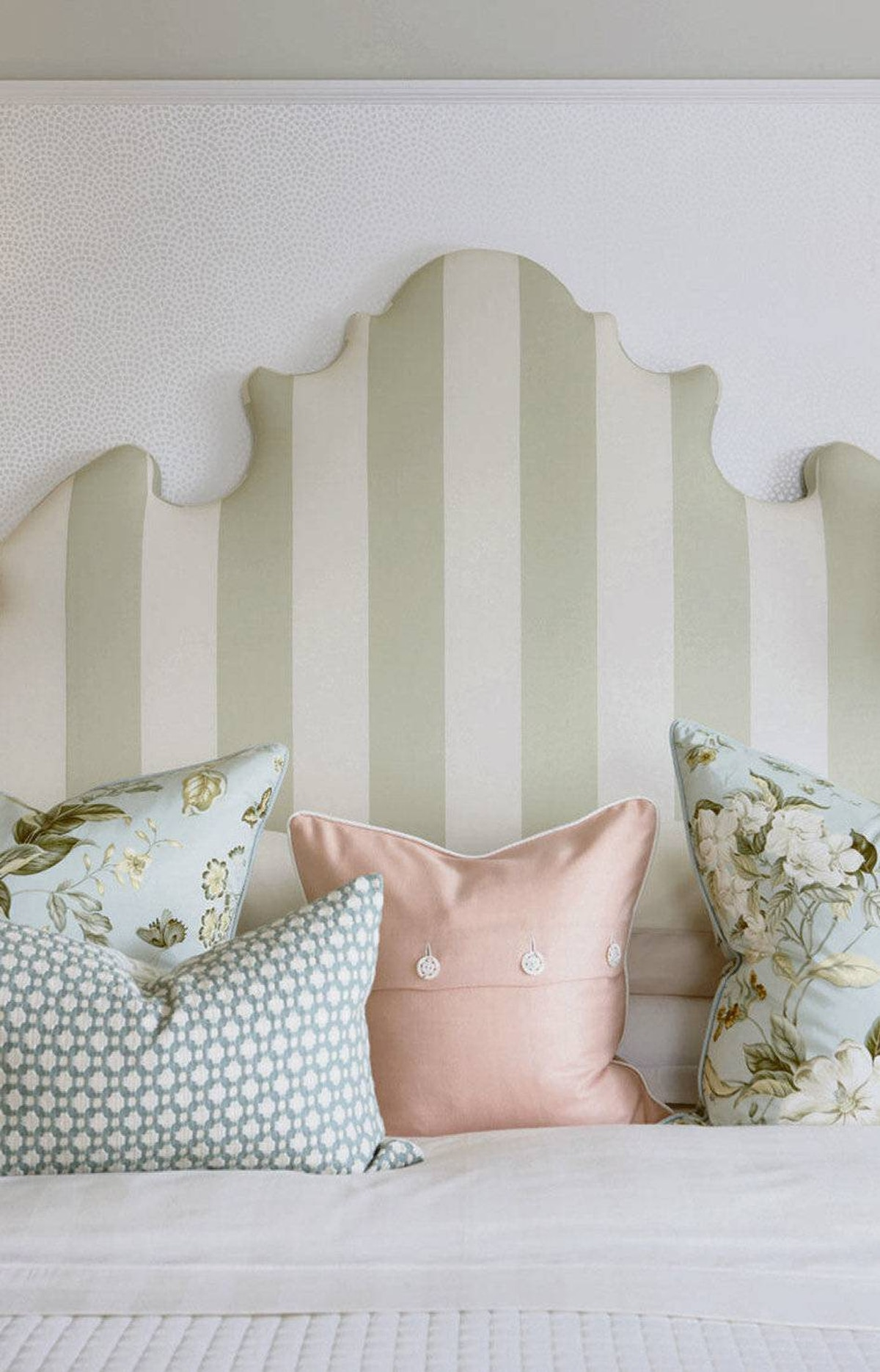 CREATE A PRETTY PALETTE Here, a wide tent stripe on a tall headboard offers the illusion of height in a room that has eight-foot-tall ceilings, while pillows sporting a graphic weave, elegant florals and a peach-toned wool gabardine top a quilted bedspread to add luxe and texture to the bed.