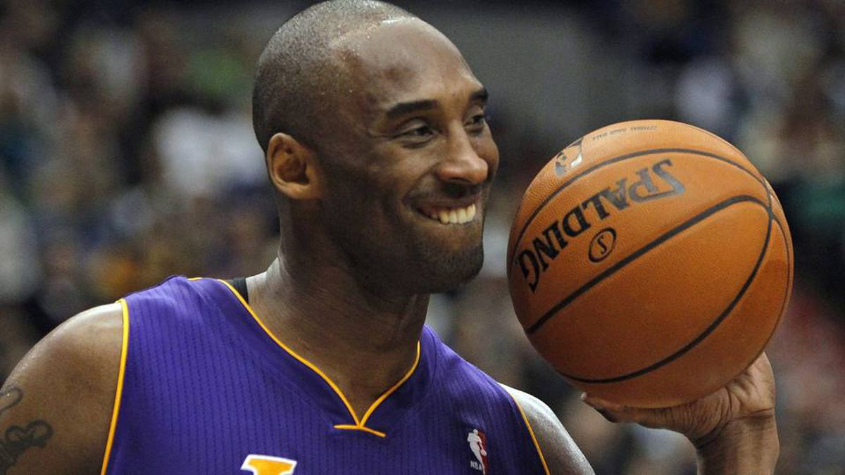 Los Angeles Lakers guard Kobe Bryant smiles as he hands the ball back to a referee during the second half of the Lakers' NBA basketball game against the Minnesota Timberwolves.