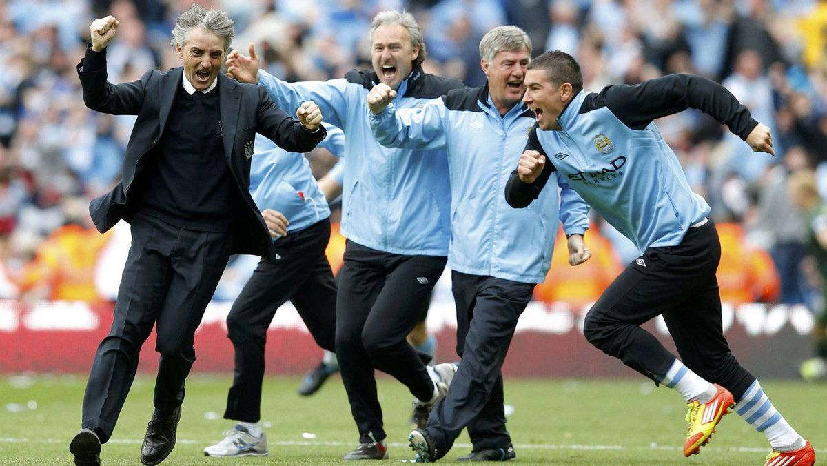 Manchester City manager Roberto Mancini (L) runs onto the pitch after winning their English Premier League soccer match against Queens Park Rangers at the Etihad Stadium in Manchester, northern England, May 13, 2012.
