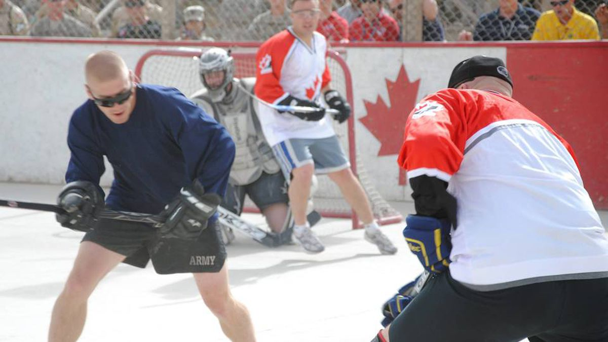 Canadian (right) and American troops face off in a ball hockey game at the military base in Kandahar, Afghanistan, Sunday, Feb.21, 2010.The game's organizers billed it as Hockey Night in Kandahar - never mind that the teams played under the blazing mid-afternoon Afghan sun - and for a couple of hours, players and fans forgot a war is raging outside the walls of this sprawling military base.