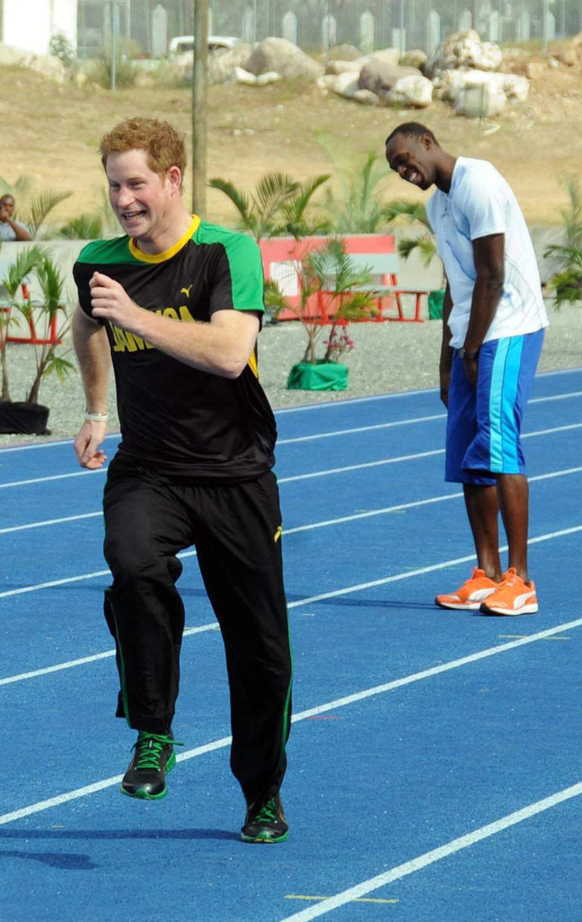 JOKER Britain's Prince Harry runs as Olympic sprint champion Usain Bolt laughs during a mock race in Kingston, Jamaica, Tuesday March 6, 2012.