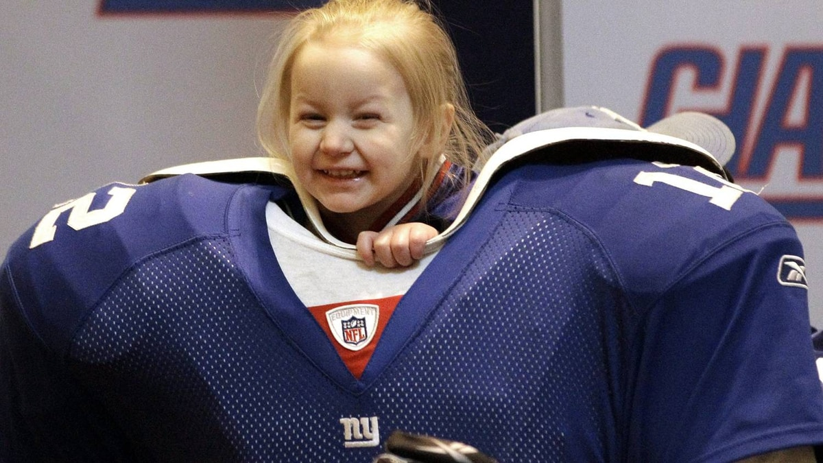 Autumn Sunshine Lubawski, 1, of Baltimore, has her picture taken with a New York Giants football player mannequin while attending the NFL Experience for Super Bowl XLVI Saturday, Feb. 4, 2012, in Indianapolis. The New England Patriots will face the New York Giants in Super Bowl XLVI on Feb. 5. (AP Photo/David J. Phillip)
