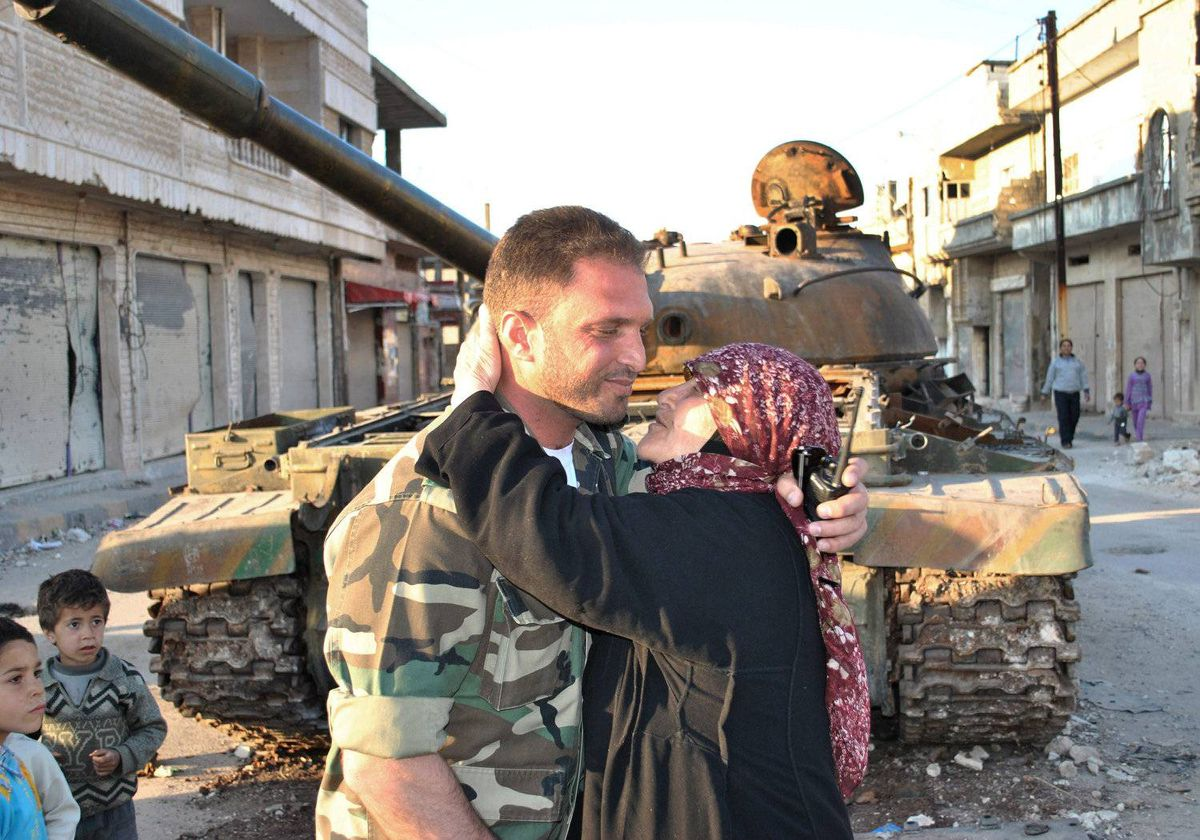 In this picture taken on Wednesday, March 21, 2012, a Syrian woman, right, kisses a soldier from the Free Syrian Army, left, in front a destroyed Syrian army forces tank which was attacked during clashes between the Syrian government forces and the Syrian rebels, in Rastan town in Homs province, central Syria.