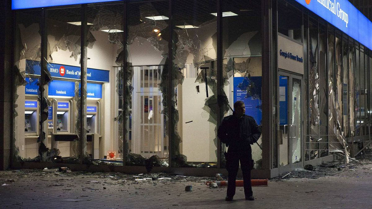 A security guard stands outside a bank damaged during riots in downtown Vancouver after the Canucks lost Game 7 of the NHL Stanley Cup Final to the Boston Bruins.