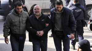 Businessman Dimitris Logothetis, centre, is escorted by plainclothes police in the northern Greek port city of Thessaloniki, Friday, Jan. 20, 2012. Greek police say they have arrested 47 people, including a senior anti-fraud official, a tax employee, a journalist and three policemen, in a crackdown on usury, extortion and money-laundering rackets.