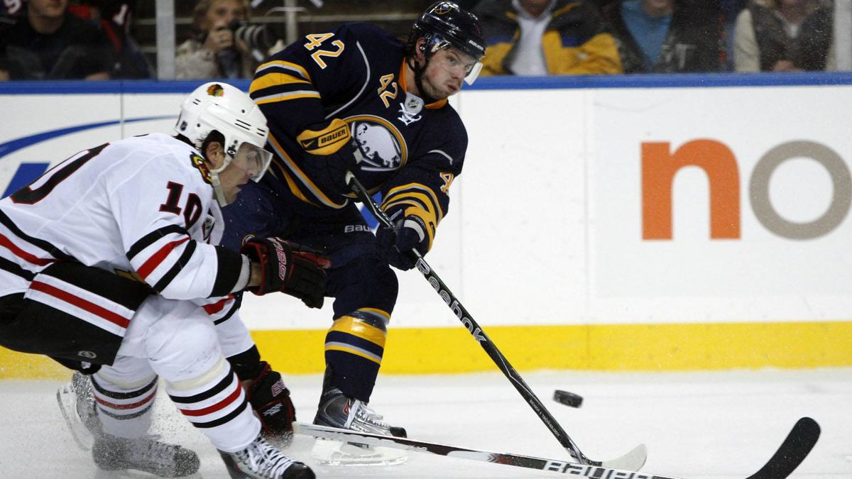 Buffalo Sabres' Nathan Gerbe (42) passes under pressure from Chicago Blackhawks' Patrick Sharp (10) during the first period of an NHL hockey game in Buffalo, N.Y., Friday, Dec. 11, 2009. (AP Photo/ David Duprey)