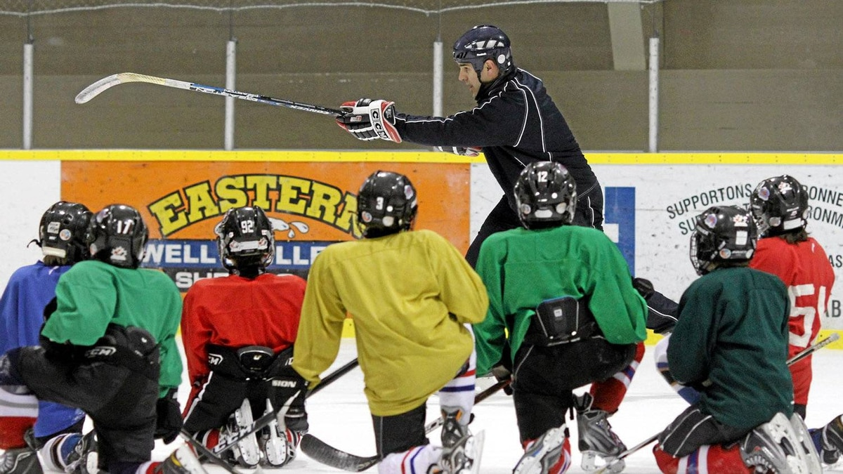 Coach Shane Doiron demonstrates a drill to his team, the Shediac Capitals in New Brunswicks' Atom Division, during practice in Shediac, New Brunswick on Monday, March 7, 2011.