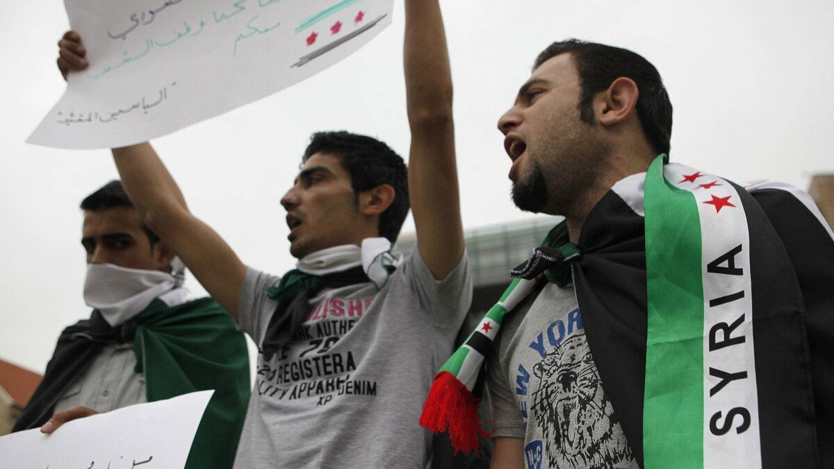 Syrian Kurds wearing Syrian opposition flags chant slogans and carry placards during a sit-in in front of the United Nations headquarters in Beirut, in solidarity with anti-government protesters in Syria, April 29, 2012.