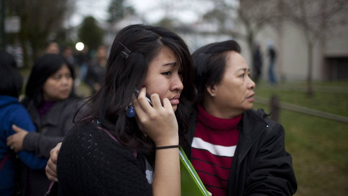A student is embraced by a family member outside Sir Charles Tupper Secondary School in Vancouver after a teenage girl said she was stabbed. The story, which turned out to be bogus, caused the school to go into lockdown on Jan. 9, 2012.