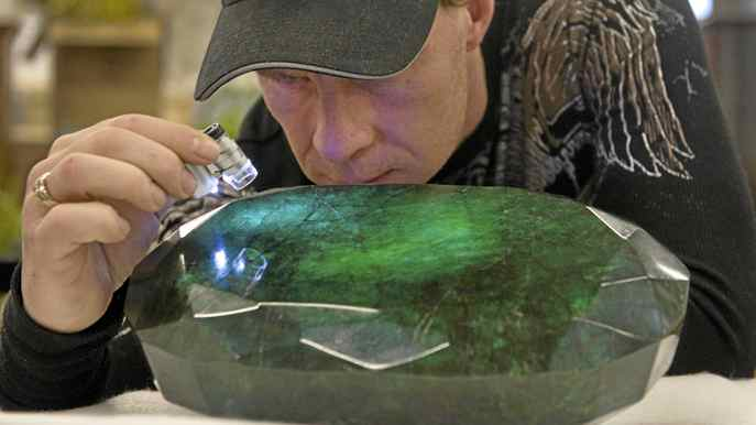 "Regan Reaney, owner of the the world's largest emerald looks over the gem at the Western Star Auction House in Kelowna, British Columbia January 26, 2012. The 57,500 carat emerald, named ""Teodora"", which weighs 11.5 kg (25.35 lb) was mined in Brazil and cut in India. The stone will be publicly auctioned this weekend."