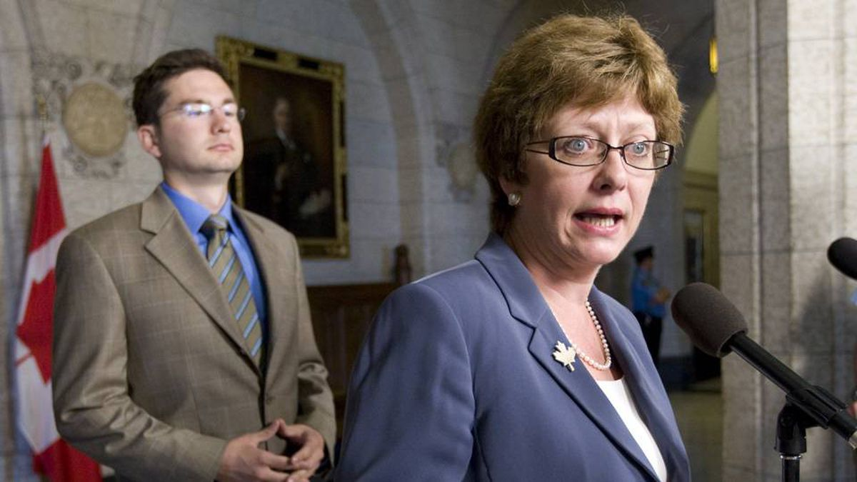 Minister of Human Resources and Skills Development Diane Finley speaks with the media about the EI working group as fellow committee member Pierre Poilievre looks on during an availability outside the House of Commons on Parliament Hill on Thursday.