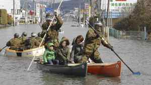 Japan Defense Force personell help people go through the flooded area by boats in Ishinomaki in Miyagi Prefecture (state), northern Japan, Saturday morning, March 12, 2011, a day after a strong earthquake-triggered devastating tsunami hit the area.