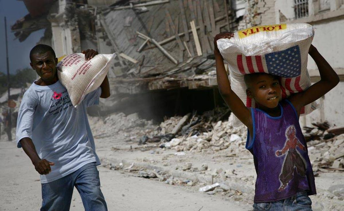 A young boy and an adult walk carrying bags of rice away from a downtown feeding centre.