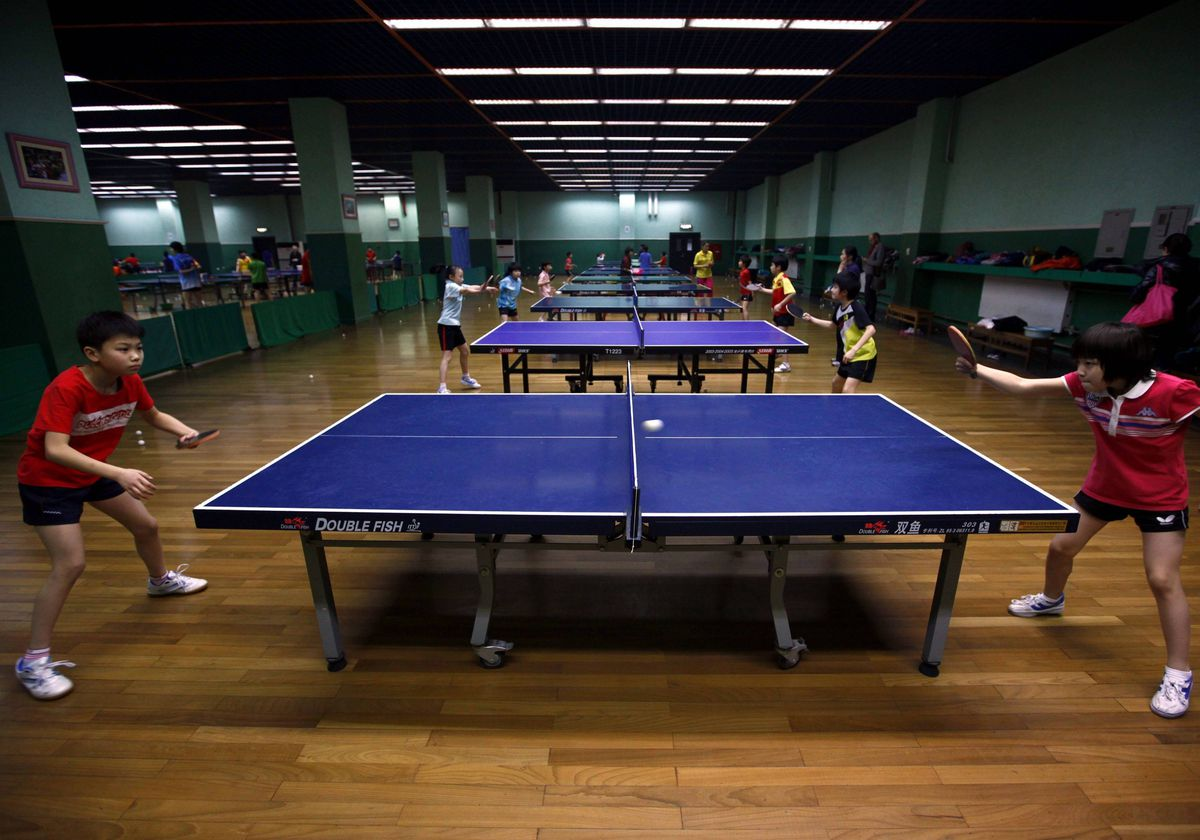 Two students practise together during a table tennis class at the Shichahai Sports School in Beijing.