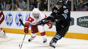 Kyle Wellwood #20 of the San Jose Sharks gets a backhand shot-off pass Jakub Kindl #4 of the Detroit Red Wings in the second period of an NHL hockey game at the HP Pavilion on March 3, 2011 in San Jose, California. The Sharks won the game 3-1.