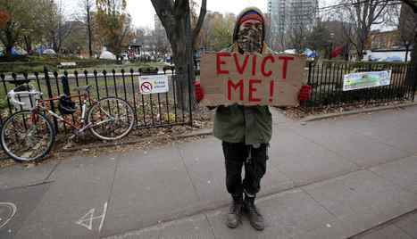 A protestor stands outside St. James Park before Toronto City bylaw officers escorted by Police came through the property posting eviction notices Monday, November 21, 2011.
