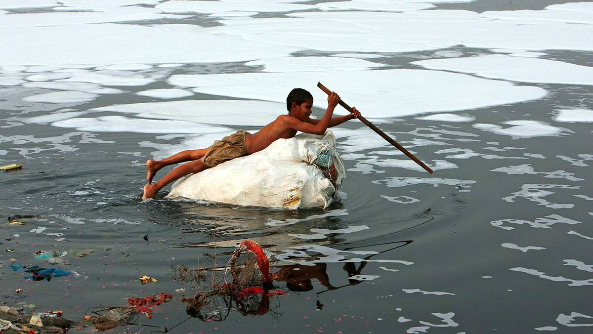 A boy looks for recyclable items in the polluted waters of the Yamuna river in New Delhi on Dec. 9, 2009.
