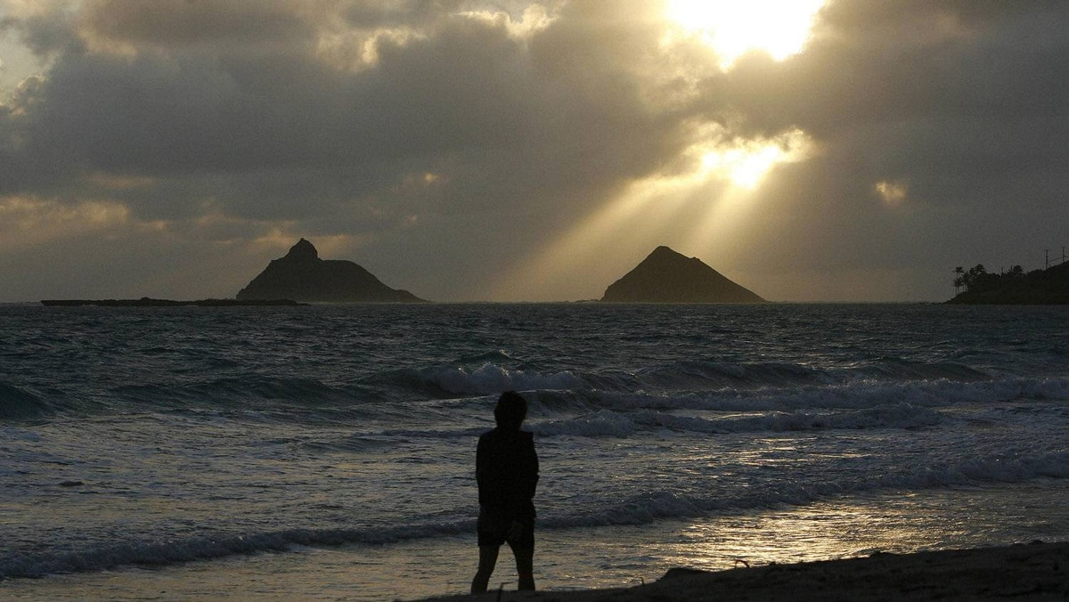 A woman walks along Kailua beach as the sun rises over the Mokulua Islands, near where U.S. President Barack Obama is staying while he is on Christmas vacation, in Hawaii, December 24, 2011.