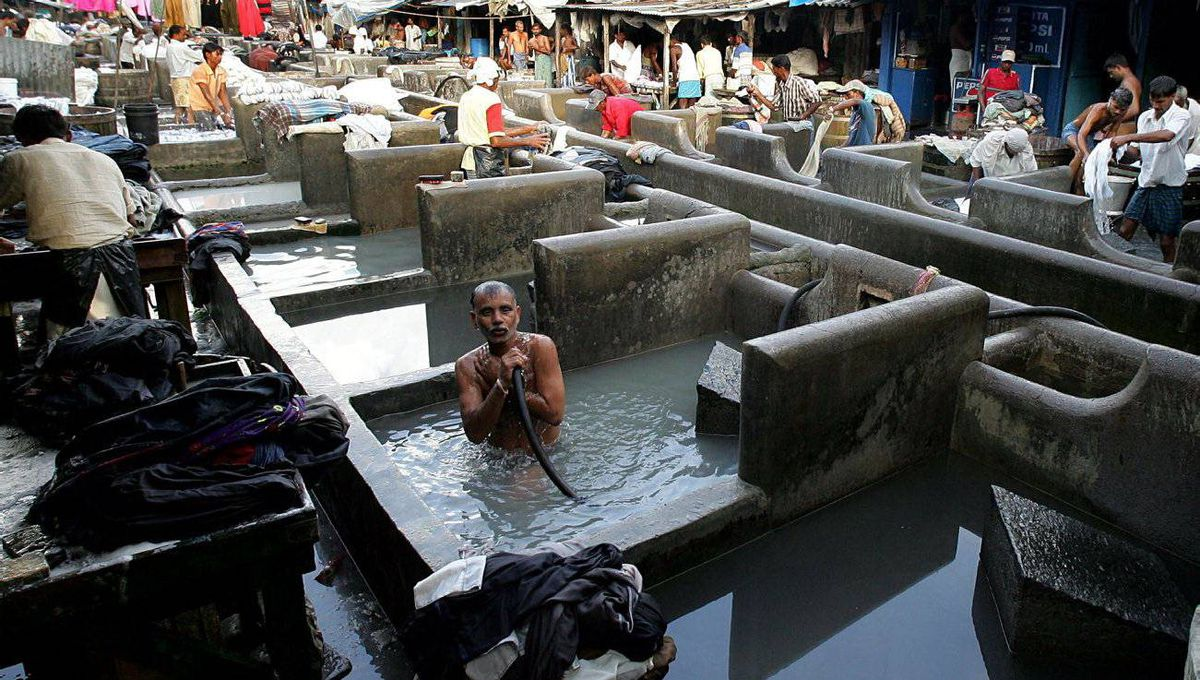 "An Indian traditional laundryman known as ""dhobi"" pours water on himself after washing clothes at dhobi ghat in Mumbai."