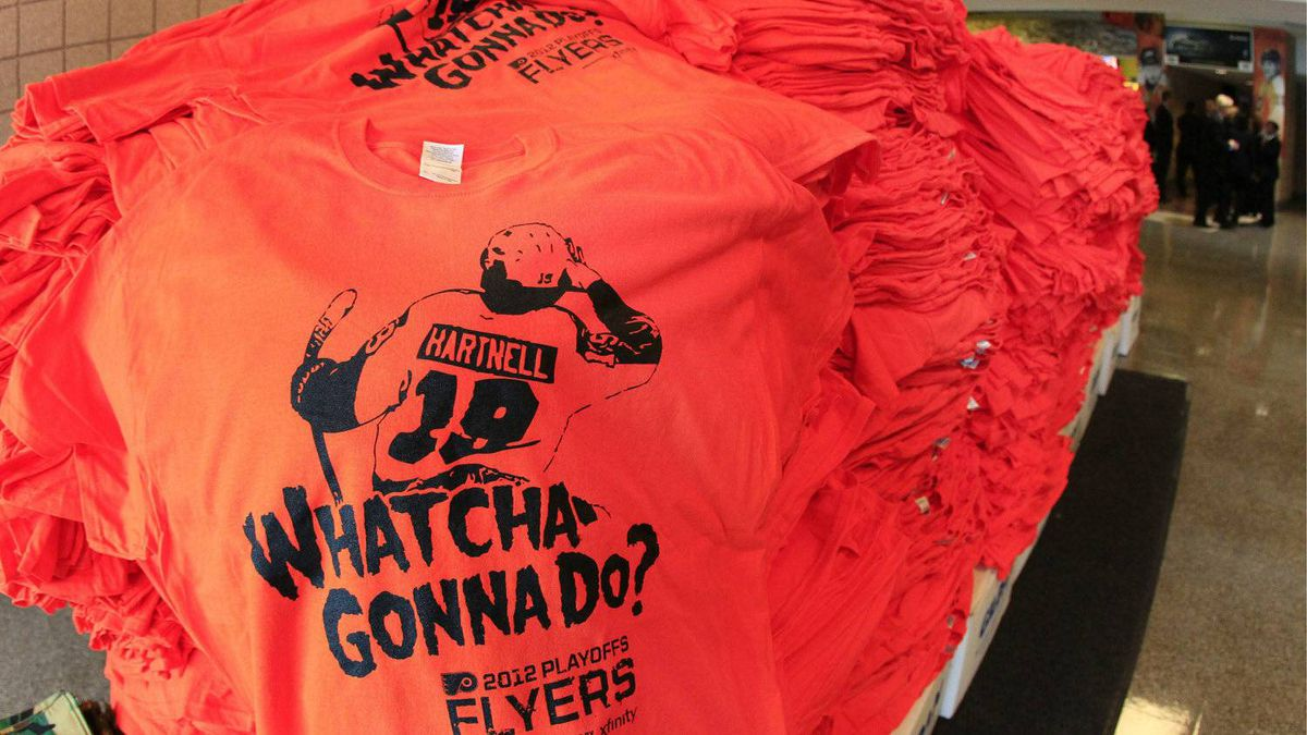 An orange T-shirt with the image of Scott Hartnell above the phrase made famous by professional wrestler Hulk Hogan rests on a pile of thousands that Philadelphia Flyers fans will get before Game 3 in a first-round NHL Stanley Cup playoffs hockey series against the Pittsburgh Penguins Sunday, April 15, 2012, in Philadelphia. (AP Photo/Tom Mihalek)