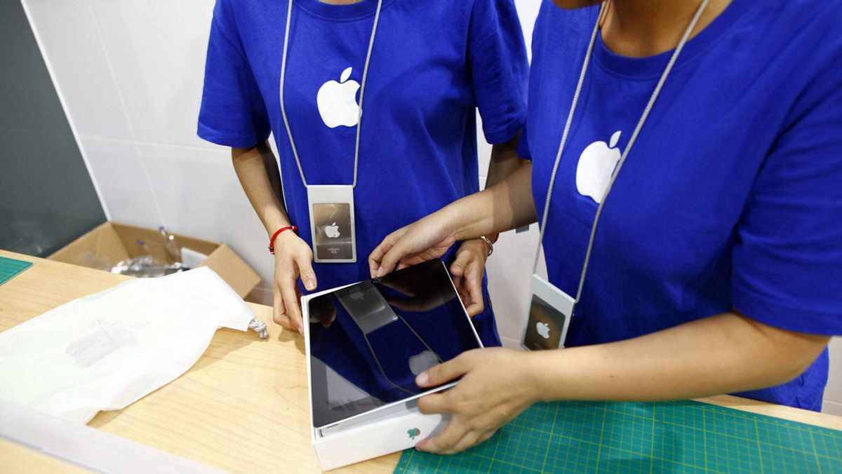 Employees look at a new iPad 2, purchased by a customer inside a fake Apple Store in Kunming, Yunnan province July 22, 2011.