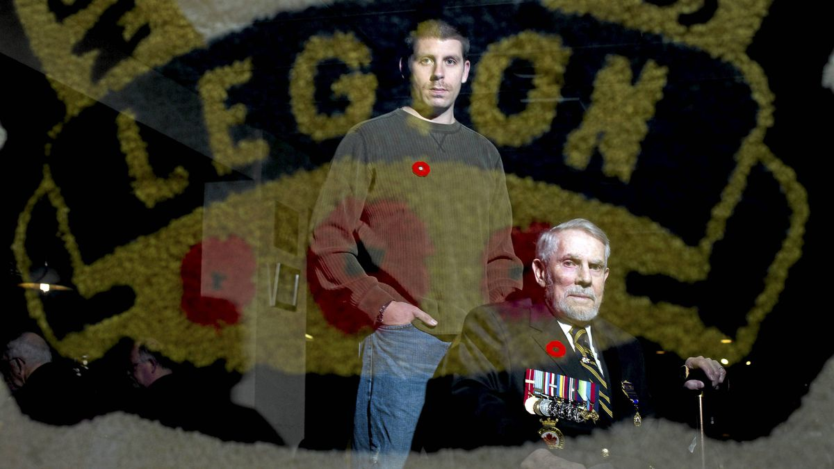 Canadian war veterans, Mat Belear, left, and Gus MacGillivary are reflected in a banner at the Legion in Amherstview near Kingston, Ont. Nov. 3/2011.