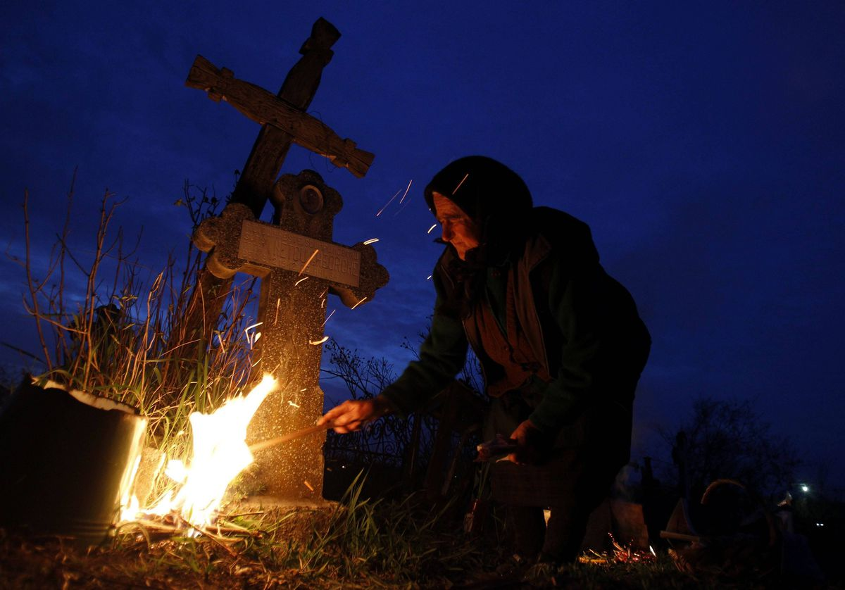 A woman lights a fire in front of the graves of her relatives at a cemetery in the village of Copaciu, 42 km southwest of Bucharest. Orthodox women went to church and cemeteries in the early morning on Maundy Thursday to light candles, burn incense and mourn their dead relatives as part of a southern Romania tradition.