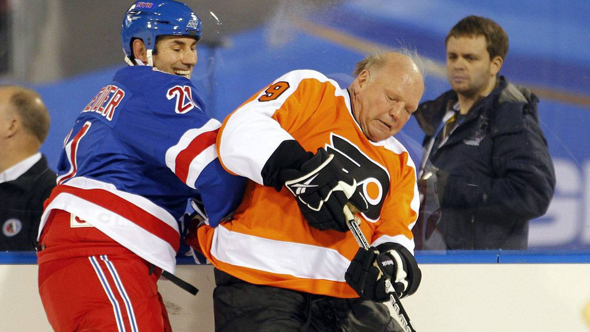 Mathieu Schnieder, left, of the New York Rangers alumni team, puts Bob Kelly, of the Philadelphia Flyers alumni team, into the boards. (AP Photo/Tom Mihalek)