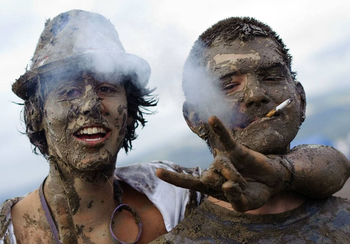 Festival-goers pose after playing in the mud during the second day of the 36th edition of the Paleo festival in Nyon, Switzerland.