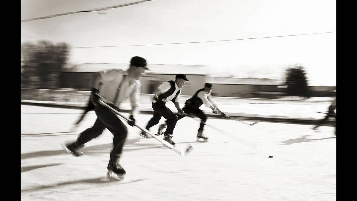 A group of Mennonite boys, aged 15-18, play a game of shinny hockey on a homemade rink on the farm owned by Noah Martin in Wallenstein, Ontario on Jan 8, 2011. (Photo by Peter Power/The Globe and Mail)