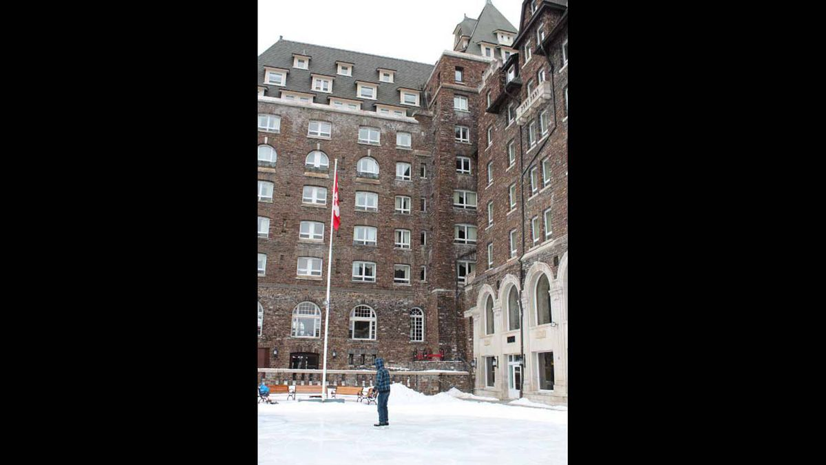 A man is learning to skate on the ice at the Banff Spring's Hotel
