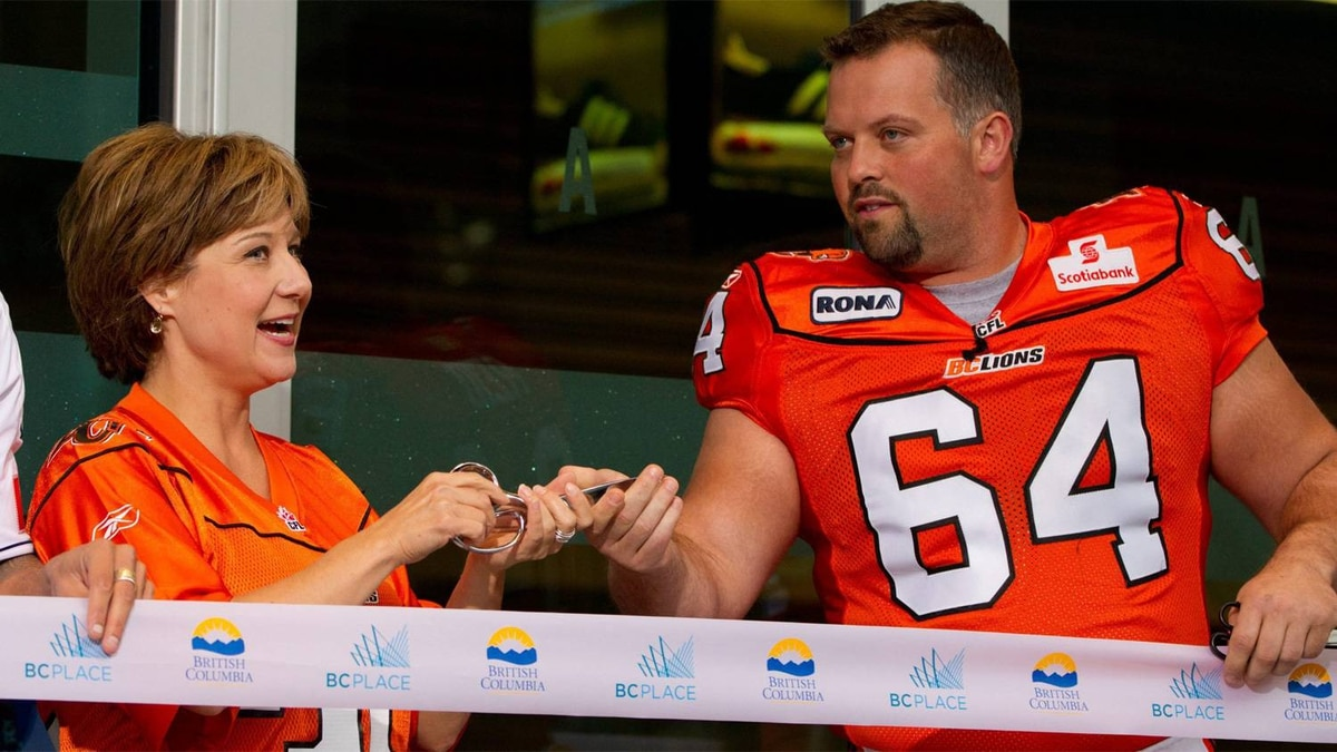 British Columbia Premier Christy Clark, left, and B.C. Lions' Angus Reid take part in a ribbon cutting to officially open the renovated B.C. Place stadium before the Lions played the Edmonton Eskimos in a CFL football game in Vancouver, B.C., on Friday September 30, 2011.