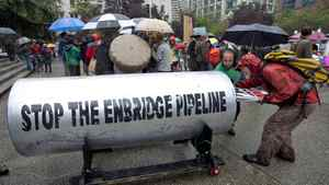 Protesters fill a giant piece of pipeline with placards after a demonstration outside the Vancouver Art Gallery on Aug. 31, 2010.