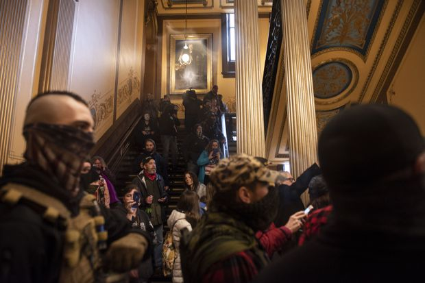 Hundreds of protesters, some carrying guns, demonstrate against Michigan's emergency measures